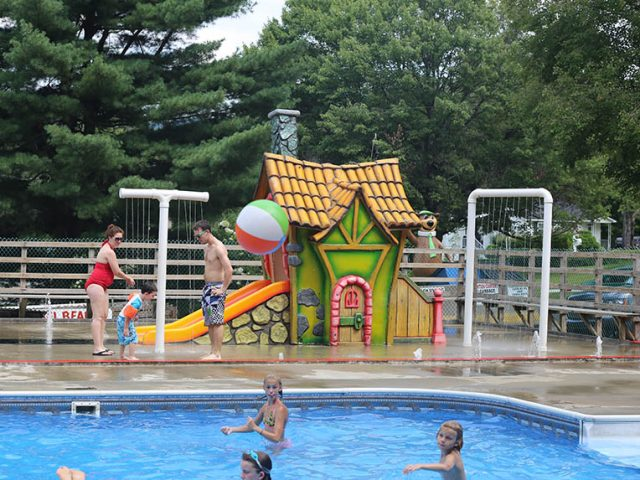 lower pool photo with slide and little house near swimming pool