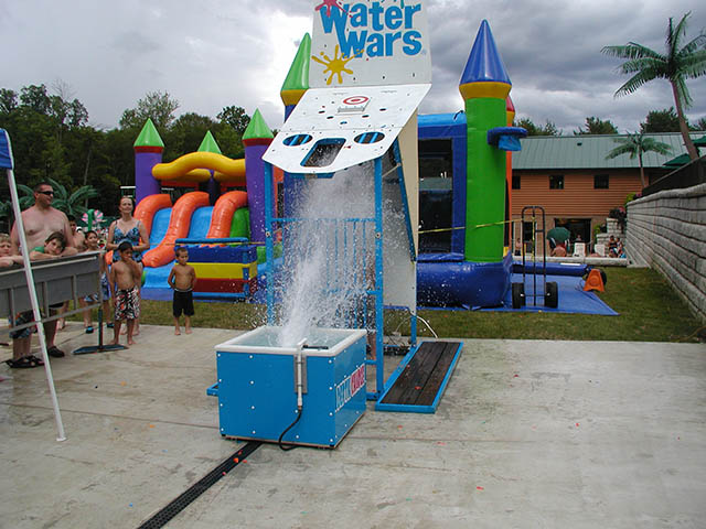 photo of waterwars spraying water with a bouncy house in the background